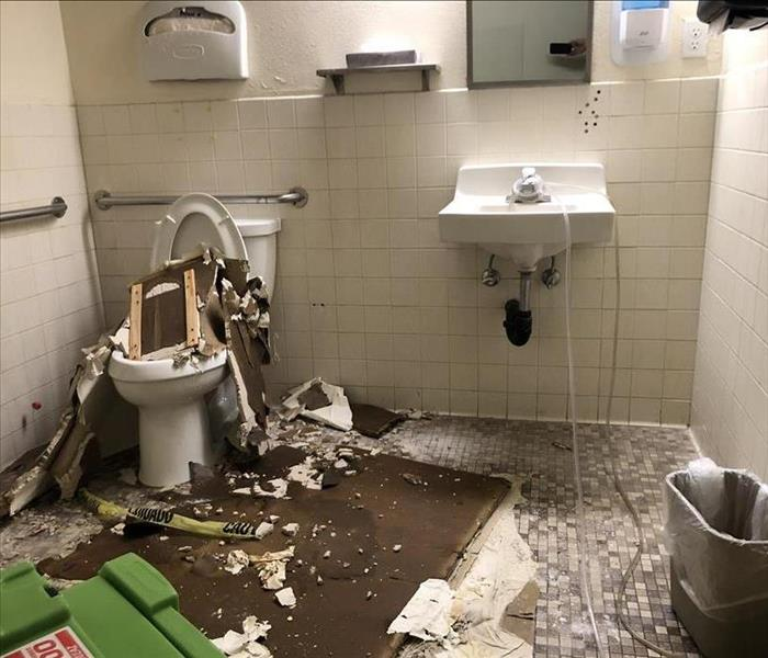 Ceiling piles of tile scattered over bathroom sink and toilet